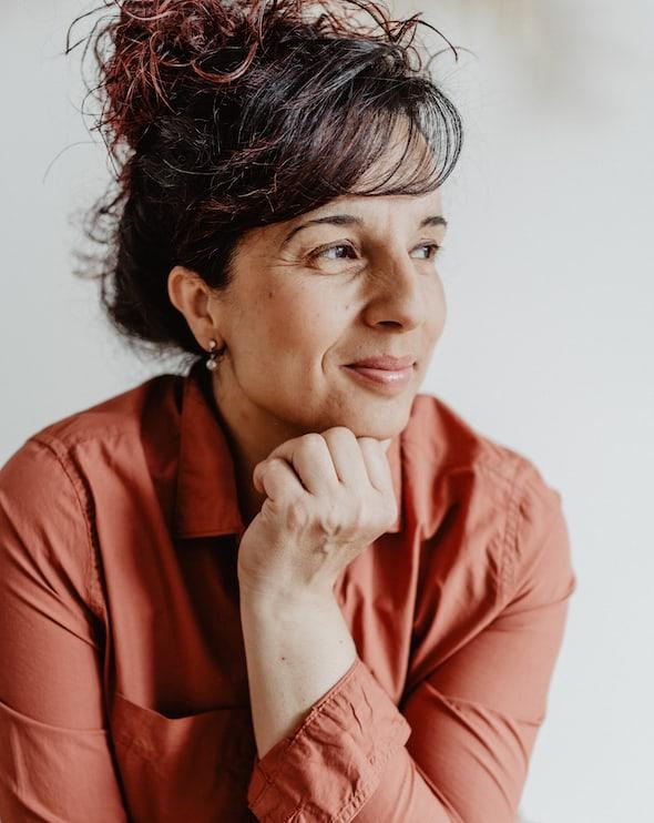 Dorina Insalaco stützt ihren Kopf auf ihrer Hand ab, schaut nach rechts und lächelt