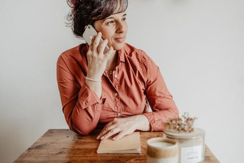 Corina Insalaco sitzt an ihrem Tisch und telefoniert mit einem Kunden