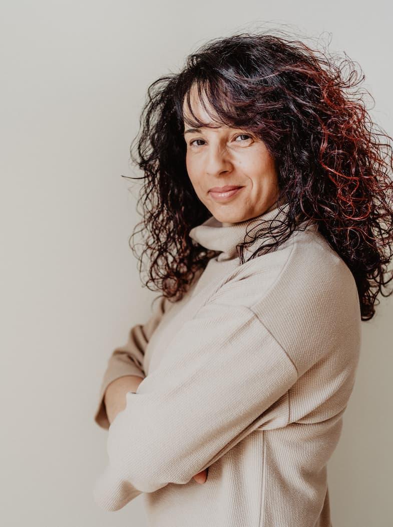 Dorina Insalaco steht seitlich mit verschränkten Armen und lächelt in die Kamera